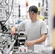 Mitarbeiter beim Befüllen eines Behälters mit Ausrüstung von Rexroth