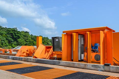 Hydraulikaggregate auf dem Damm: Die Einhausungen sind klimatisiert und schützen die Anlage vor dem tropischen Wetter.